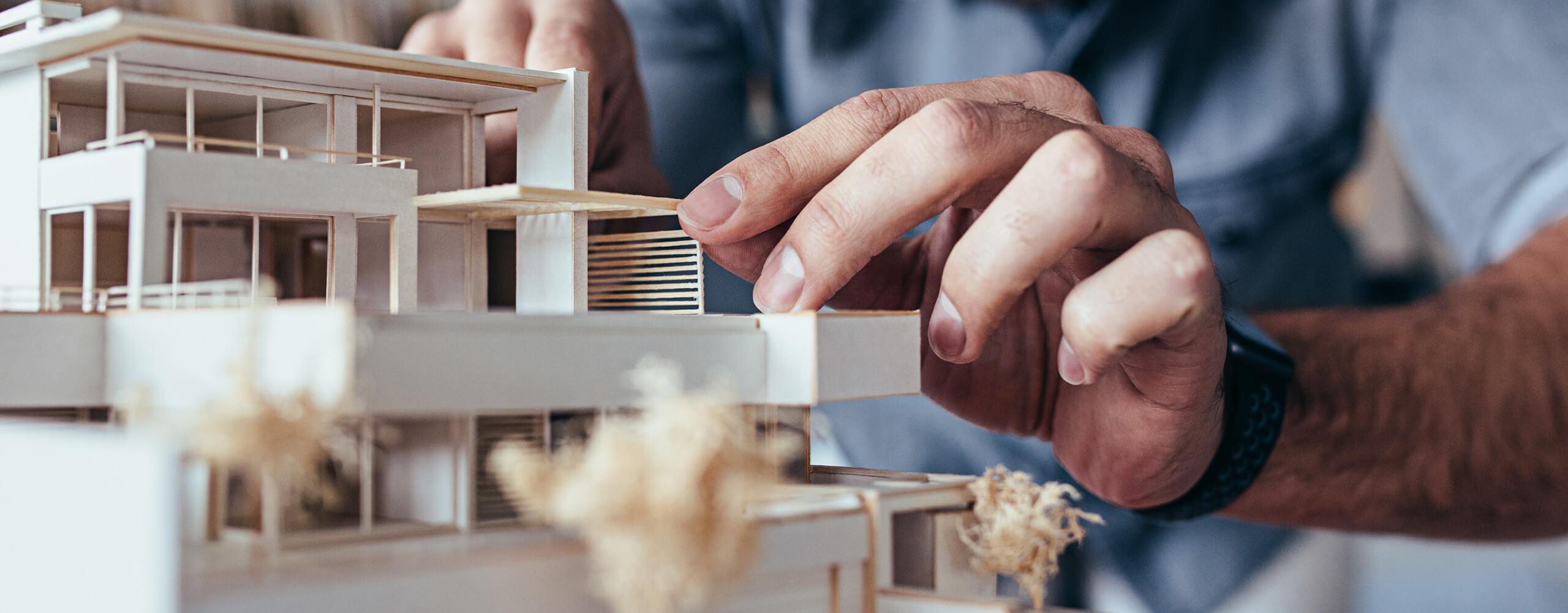 Nahaufnahme von Händen an einem Stadtmodell